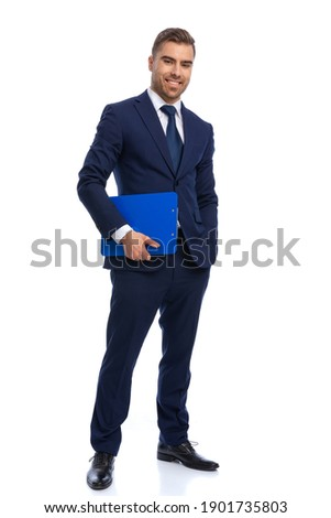 full body picture of smiling businessman in elegant navy blue suit holding clipboard and posing with hand in pocket on white background in studio