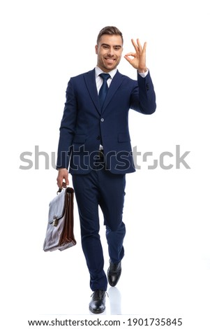 full body picture of elegant man in navy blue suit holding briefcase, making ok gesture and smiling, walking isolated on white background in studio