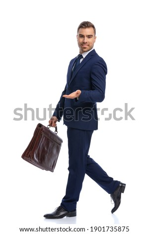 full body picture of bearded man in navy blue suit presenting to side, holding suitcase and smiling, walking isolated on white background in studio