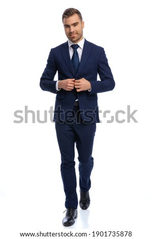 full body picture of unshaved young man smiling and adjusting navy blue suit, walking isolated on white background in studio