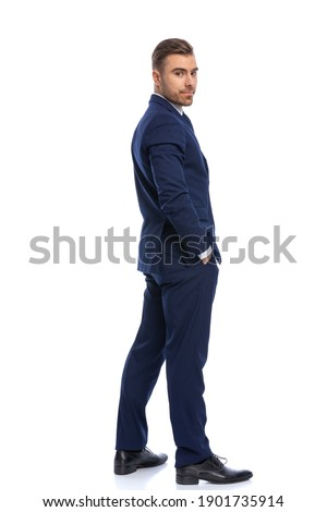 full picture of happy young guy in navy blue suit holding hands in pockets and looking over shoulders, standing isolated on white background in studio