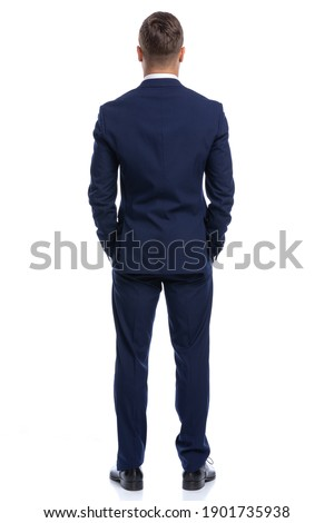 full body picture of back view of young businessman in navy blue suit holding hands in pockets, standing isolated on white background in studio