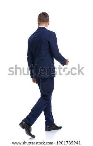 full body picture of elegant fashion model in navy blue suit walking isolated on white background in studio