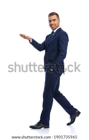 full body picture of elegant businessman in navy blue suit holding hand up, presenting and inviting, smiling and walking isolated on white background in studio