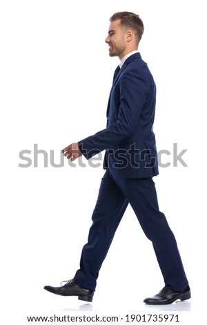 full body picture of elegant young man in navy blue suit looking to side and walking isolated on white background in studio
