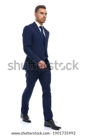 full body picture of elegant young businessman in navy blue suit walking isolated on white background in studio