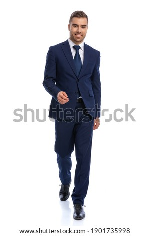full body picture of happy young businessman in navy blue suit walking and smiling isolated on white background in studio