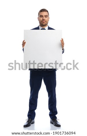 full body picture of proud businessman in navy blue suit smiling and presenting empty board, standing isolated on white background in studio