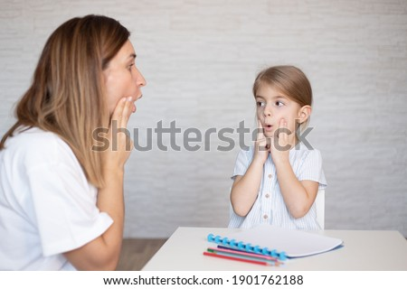 Young women with child make speech therapy exercises at home. Royalty-Free Stock Photo #1901762188