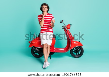 Full length body size view of handsome cheery guy sitting moped using gadget blogging isolated over bright green turquoise color background