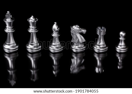 Silver chess pieces six different types used on chessboard to play the game of chess. left to right: king, queen, bishop, knight, rook, pawn isolated on black background