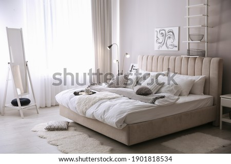 Cozy bedroom interior with beautiful picture and large mirror