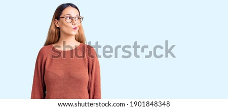 Beautiful young woman wearing casual clothes and glasses smiling looking to the side and staring away thinking.  Royalty-Free Stock Photo #1901848348
