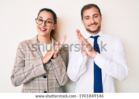 Beautiful couple wearing business clothes clapping and applauding happy and joyful, smiling proud hands together  Royalty-Free Stock Photo #1901849146