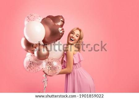Carefree young lady with holiday balloons partying, celebrating birthday or anniversary over pink studio background. Beautiful female model having special festive occassion, enjoying her birthday Royalty-Free Stock Photo #1901859022