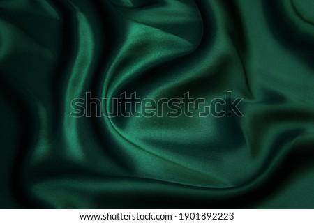 Texture, background, pattern. Texture of green silk fabric. Beautiful emerald green soft silk fabric. Royalty-Free Stock Photo #1901892223