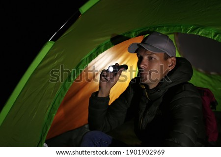 Man with flashlight sitting in tent at night Royalty-Free Stock Photo #1901902969