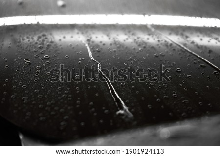 Streams and drops of water on a gray car, macro photography.