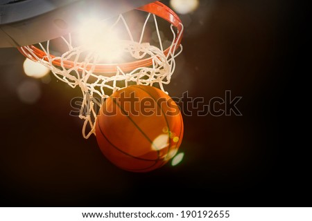 Basketball going through the basket at a sports arena (intentional spotlight)