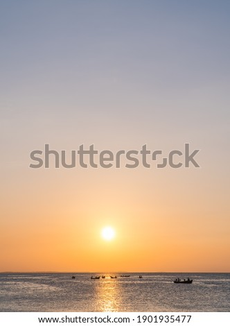 Sunset sky vertical over sea in the evening and fishing boat with colorful orange sunlight and sundown landscapes,Dusk sky. Royalty-Free Stock Photo #1901935477