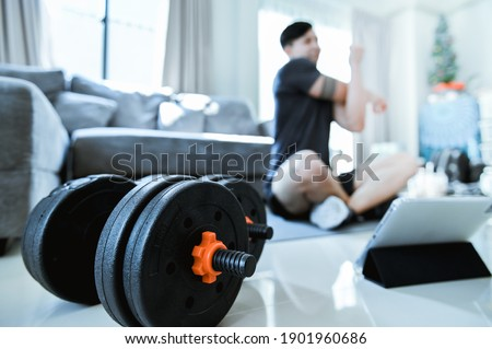 Exercises at Home. Active Asia man in T-shirt and Shorts is warming up stretching watching fitness video tutorial online on tablet in living room. dumbbells on pictures lying on floor.