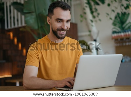 Attractive smiling man using laptop computer, working from home. Portrait of young freelancer copywriter typing, sitting at workplace. Student studying, distance learning, searching, online education