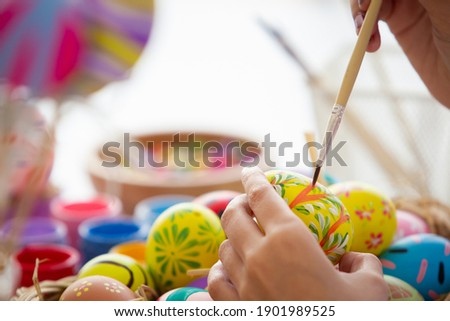 Asian young pretty woman enjoy painting a water colors on fantasy eggs for Easter egg festival. Beautiful colorful fancy Easter egg in bucket. The symbolic of Easter egg festival concept. Royalty-Free Stock Photo #1901989525