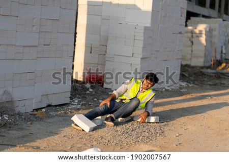 Foreman, a man walking in a construction project, falls into a brick-and-mortar accident during work, injured his ankle. Royalty-Free Stock Photo #1902007567
