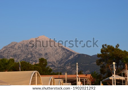 Landscape - village in the mountains, blue sky, green plants. View of Mount Olympus, Tekirova (Turkey, Antalya, Kemer). Mediterranean coast of Lycia, Tahtali mountains. View from the beach Royalty-Free Stock Photo #1902021292