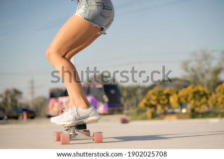 Close-up Asian women surf skate or skates board outdoors on beautiful summer day. Happy young women play surf skate at park on morning time.
