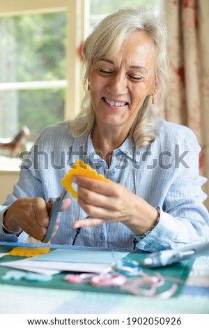 Senior Woman Doing Craft Scrapbooking Or Making Greetings Card  At Home Royalty-Free Stock Photo #1902050926