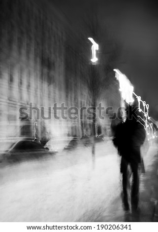 Art photo.Silhouette of a man walking at night on the wet asphalt.