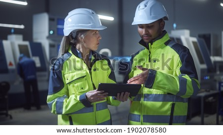 Chief Engineer and Project Manager Wearing Safety Vests and Hard Hats, Use Digital Tablet Computer in Modern Factory, Talking, Optimizing Production Line. Industrial Facility with CNC Machinery Royalty-Free Stock Photo #1902078580