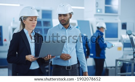 Chief Engineer and Project Manager Wearing Safety Vests and Hard Hats, Use Laptop in Modern Factory, Talking, Optimizing Production Line. Industrial Facility: Professionals Working on Machinery Royalty-Free Stock Photo #1902078652