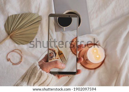Woman hand taking picture of composition with cinnamon bun, coffee and burning candle on the bed. Blogger taking lifestyle photo for social media