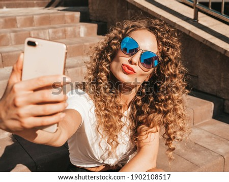 Beautiful smiling model with afro curls hairstyle dressed in summer hipster clothes.Sexy carefree model sitting on  stairs in the street in sunglasses.Taking selfie self portrait photos on smartphone