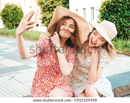Two young beautiful smiling hipster female in trendy summer sundress.Sexy carefree women sitting on street background in hats. Positive models taking selfie self portrait photos on smartphone