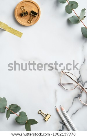 Flat lay home office desk table. Feminine workspace with glasses, office supplies, greenery on marble background. Elegant freelancer workplace Royalty-Free Stock Photo #1902139978