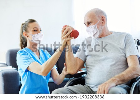 Doctor or nurse caregiver exercise with senior man, both wearing protective masks,  at home or nursing home Royalty-Free Stock Photo #1902208336