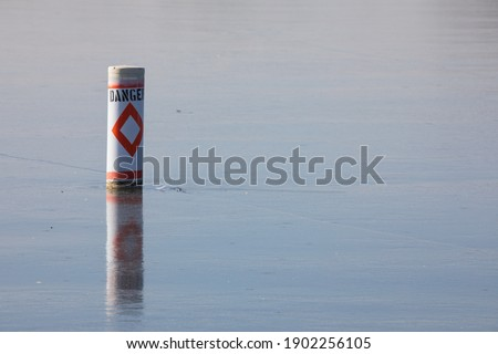 Danger buoy locked in ice.  Reflection of marker in the ice.  Blue sky reflected in the cracked ice.  Winter scene with a warning flotation device. Royalty-Free Stock Photo #1902256105