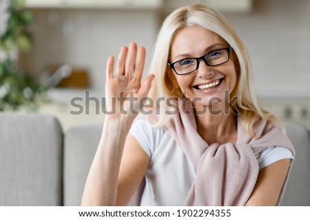 Webcam portrait of a happy mature caucasian blonde woman wearing eyeglasses, sitting on couch, looking directly at camera with friendly smile, waving hand, greeting gesture Royalty-Free Stock Photo #1902294355