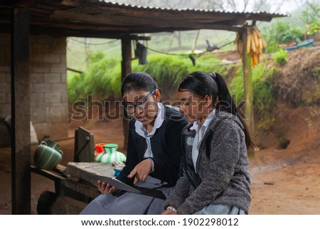 Girls students doing their homework with a digital tablet at home. Royalty-Free Stock Photo #1902298012