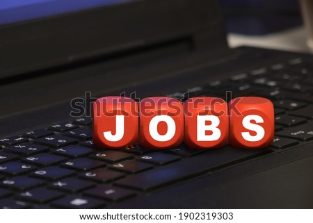 dice with letters JOBS on a keyboard - job search and online application Royalty-Free Stock Photo #1902319303