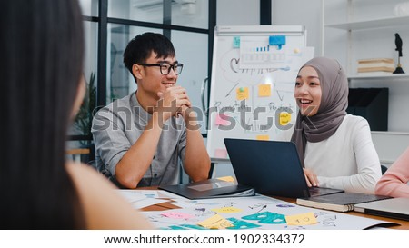 Multiracial group of young creative people in smart casual wear discussing business brainstorming meeting ideas mobile application software design project in modern office. Coworker teamwork concept. Royalty-Free Stock Photo #1902334372