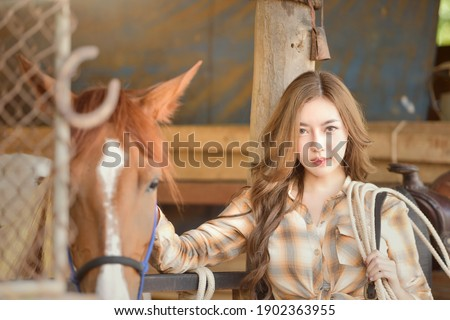 Beautiful asian woman spending a tranquil moment with a horse.Pretty Asian woman petting horse in a farm.