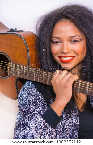 A vertical closeup of a young smiling Hispanic female posing at the camera holding a guitar on her shoulder