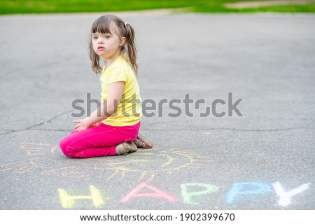 Little girl with syndrome down draws with chalk on the asphalt. Empty space for text.