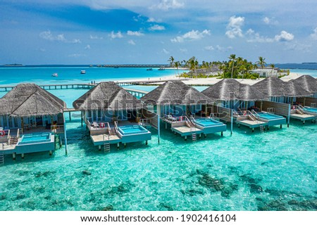 Aerial view of Maldives island, luxury water villas resort and wooden pier. Beautiful sky and ocean lagoon beach background. Summer vacation holiday and travel concept. Paradise aerial landscape pano Royalty-Free Stock Photo #1902416104