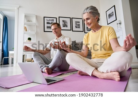 Happy old middle aged senior 50s couple learning to meditate at home watching live online tv yoga class tutorial on website looking at laptop computer doing virtual training fitness workout exercises. Royalty-Free Stock Photo #1902432778