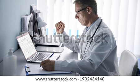 Serious mature old doctor physician using laptop tech in hospital office. Senior middle aged male gp checking patient clinical registration form, elearning working looking at computer sitting at desk. Royalty-Free Stock Photo #1902434140